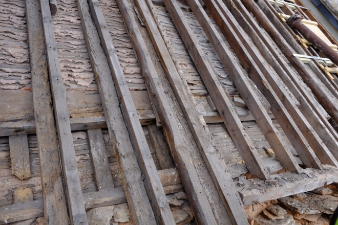 The sixteenth–century roof purlins and rafters are still doing their original job underneath later roof coverings. Later rafters (the horizontal timbers side-by-side here) were added over the centuries to strengthen the roofs and ceilings, much the same way that the current roof restoration is adding new timbers to the old where necessary. (Courtesy of Architectural Thread)