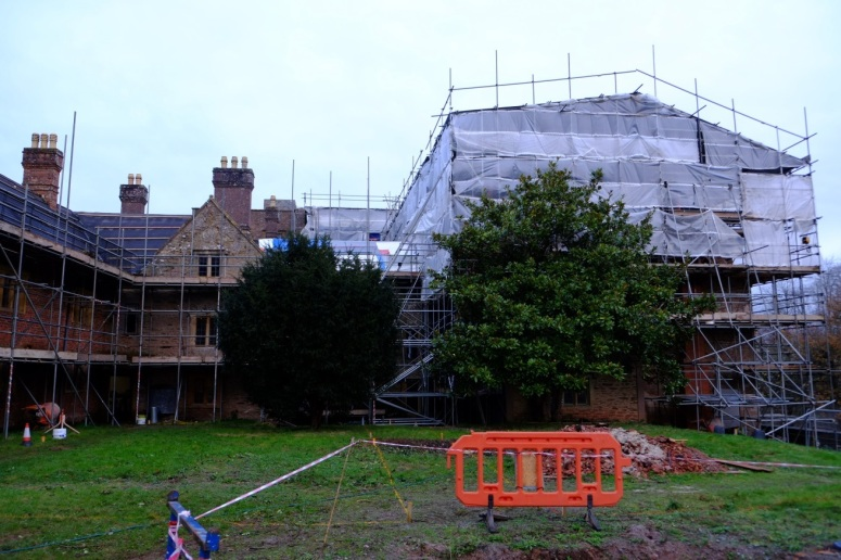 The south range in late 2015, covered in scaffolding to repair and restore the roof and stonework. This image was taken before the removal of the incorrectly placed bushes and trees that hid the old manor from view and natural light.