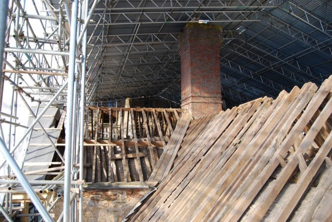 Photo taken from the south looking north; from the lower right, this photo shows the eastern gabled tower of the south range where that roof meets the chimney stack that served the1590's kitchen, housed under the roofing on the left in this photo, which is the eastern section of the south range. (Courtesy of Architectural Thread)