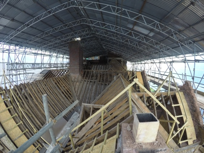Looking from south to north, this photo takes in the whole east range to the right and the eastern south-range gabled tower to the left. The thin and light coloured timber rafters are from the 1920's roof repairs, the date the chimney stacks were re-built in brick above the roof level. Those timbers sit beside earlier rafters, below which are the much heavier original sixteenth century structural timbers. (Courtesy of Architectural Thread)