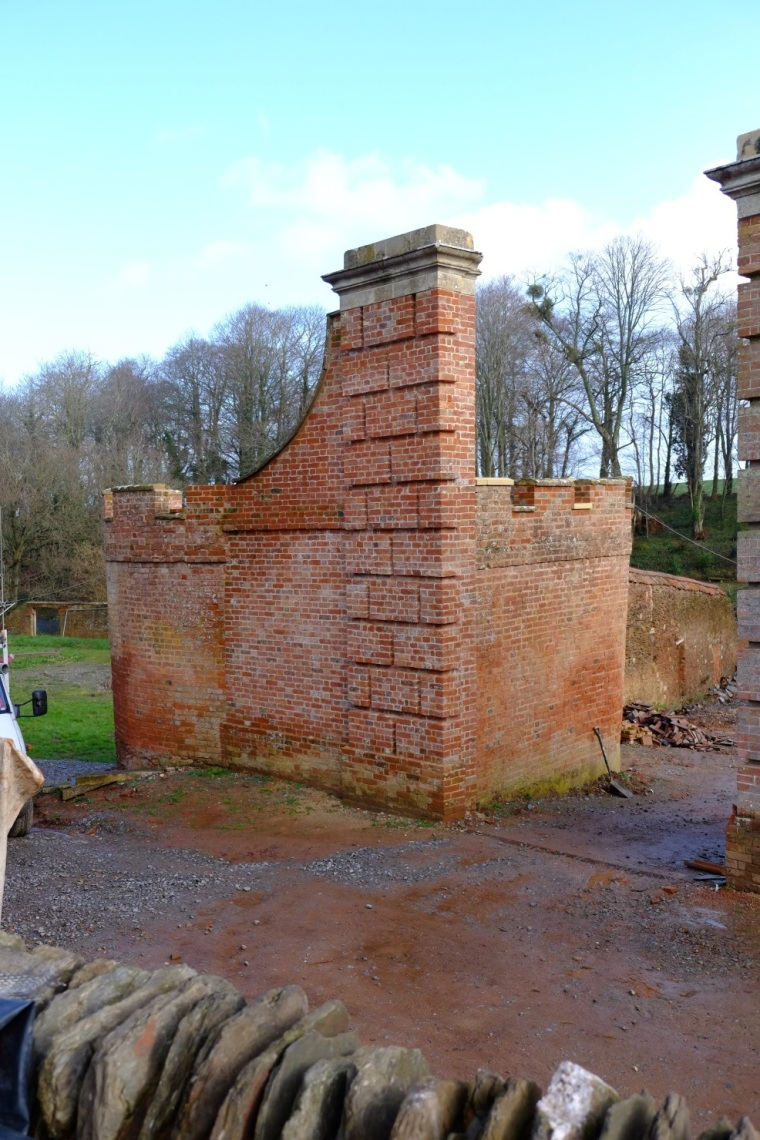 The northern most gate pillar, attached to what was the electricity sub-station from c.1950-2015, had a precipitous lean and had to be kept upright by scaffolding in order to keep it from collapsing completely. In 2015 this pillar we took this down brick by brick to its foundations so that essential repairs to re-straighten its angle could be undertaken. The pillar was then painstakingly re-built brick by brick in to their original positions and re-capped with its original stone entablature. The work carried out on this pillar included the complete restoration of the 'Cider House'.