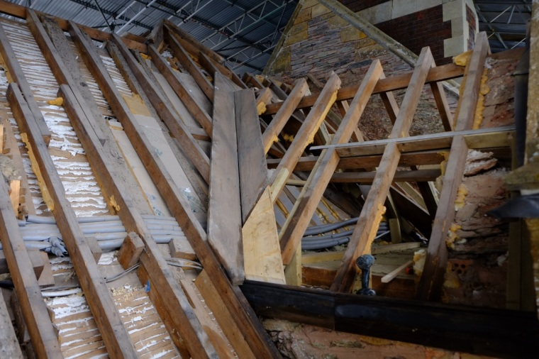 1. The gable straightened and restored and the wood and stone restorations complete, the voids between the rafters and the slates are prepared for insulation, felt and batons. (Courtesy of Architectural Thread.)